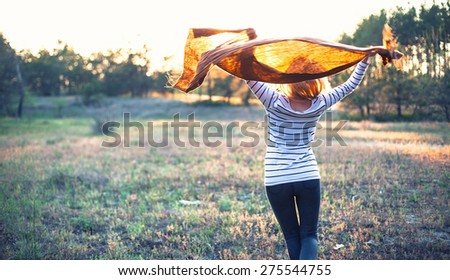 The beautiful girl with a scarf walks in forest - stock photo