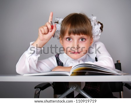 The beautiful girl with books sits at a school table - stock photo