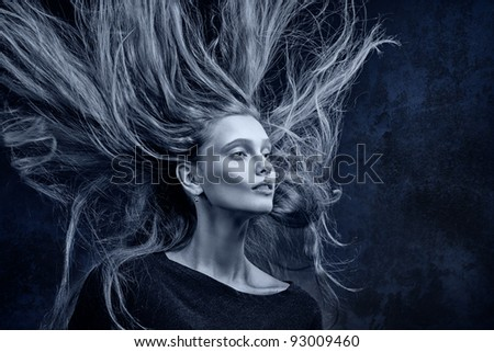 The beautiful girl with flaying hair near to a concrete wall. Dark blue toning.