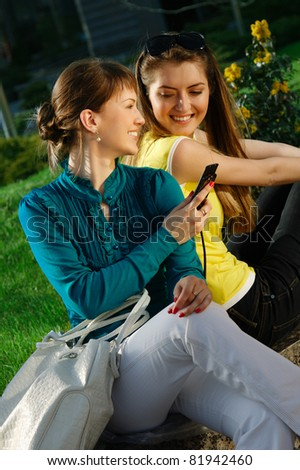 The beautiful girl with purchases and talking with cellphone - stock photo