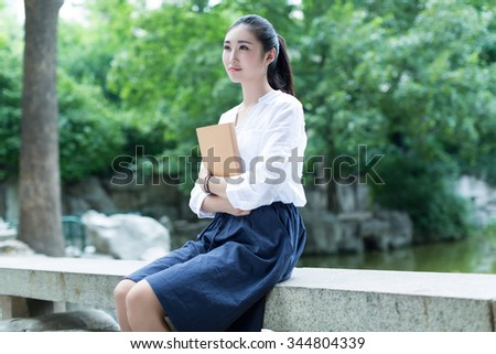 The beautiful lake, a chinese girl looking at her magazine - stock photo
