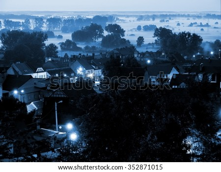 The beautiful landscape of a small town Czarnkow and the fog in the Valley of Notec river in Poland by evening. Blue filter effect