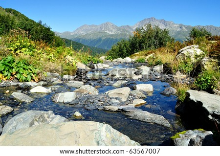 The beautiful landscape of pure mountain stream, washing the large stones,against the backdrop of high mountains - stock photo
