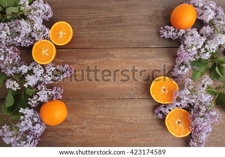 The beautiful lilac, the orange on a wooden background - stock photo