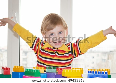The beautiful little boy poses on a light background - stock photo