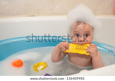 The beautiful little girl bathes in a blue bath with a toy - stock photo