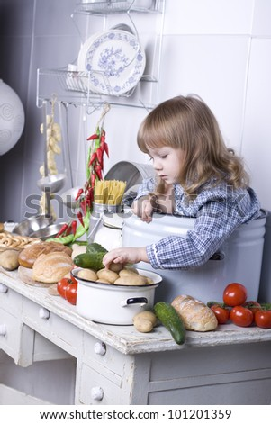 the beautiful little girl sits in a big pan on a table not to kitchen