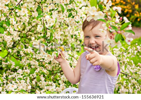 The beautiful little girl with bush blossoming tree and dandelion