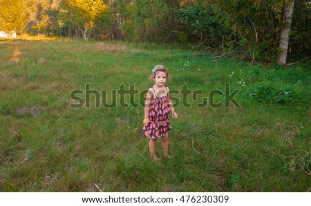 The beautiful little girl with hair, lungs as a fuzz, walks in the open air