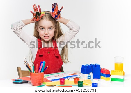 The beautiful little girl with hands in the paint - stock photo