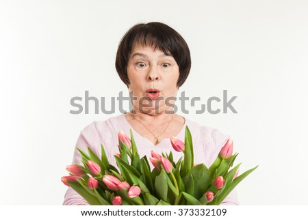 the beautiful mature woman is surprised to a bouquet of tulips - stock photo