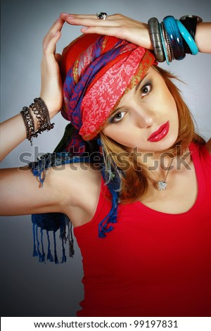 The beautiful modern girl with a bright make-up in east national scarf - stock photo