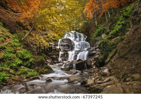 The beautiful mountain waterfall among color wood. - stock photo