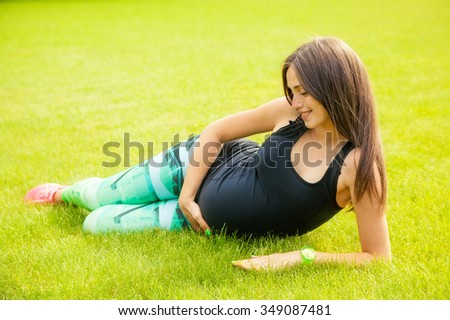 The beautiful pregnant woman plays sports outdoors - stock photo
