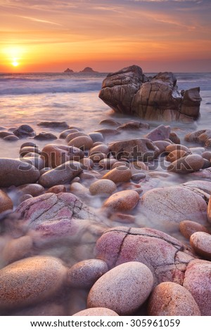 The beautiful rocky beach of Porth Nanven in Cornwall, England at sunset. - stock photo