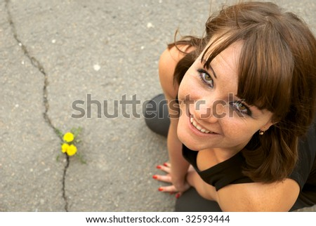The beautiful Russian girl in a black vest with a yellow flower