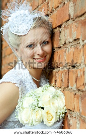 The beautiful smiling bride leaning against a wall and holding a bunch of flowers; wedding day - stock photo