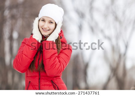 The beautiful smiling woman on walk in winter wood
