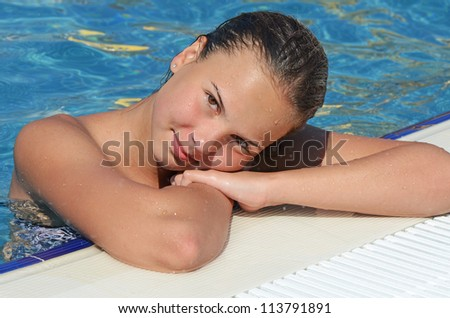 The beautiful smiling young girl in pool - stock photo