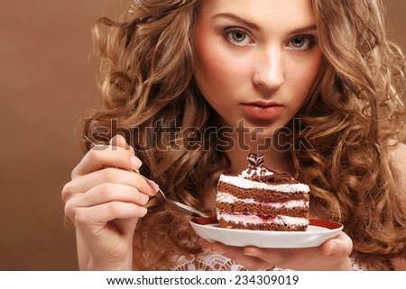 The beautiful smiling young woman with a cake - stock photo