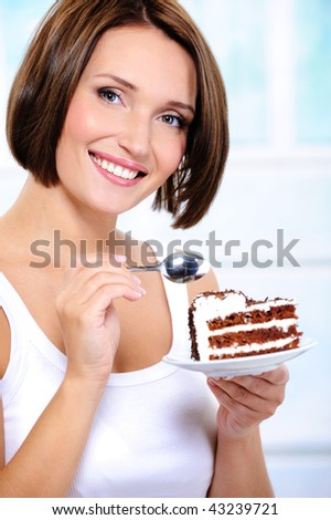 The beautiful smiling young woman with a cake slice on a plate - stock photo