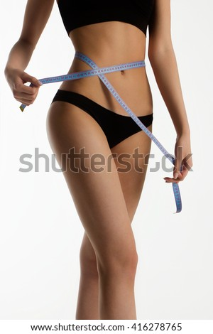 The beautiful sports woman measures a figure by the blue measuring instrument. Narrow waist, thin legs of a suntanned body. Sport, diets, weight loss. - stock photo