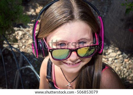 the beautiful stylish girl in big earphones, was photographed on the street, on walk