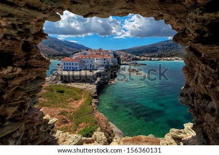 The beautiful town of Chora in Andros island, Cyclades, Greece, built on a cape, viewed from a ruin - stock photo