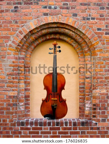 The beautiful violin in the blind window in the old brick wall - stock photo