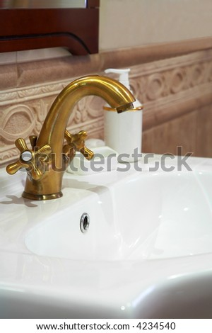 The beautiful water faucet from bronze in a bathroom - stock photo