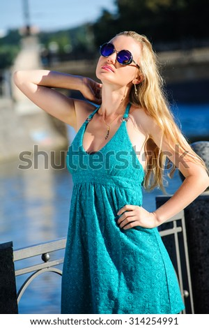 The beautiful woman in elegant blue dress in the summer city - stock photo