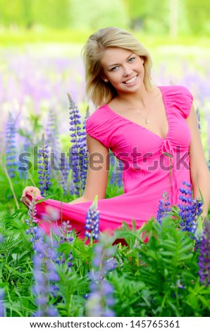 The beautiful woman in field with lupin