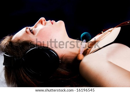 The beautiful woman listens to music through headphones