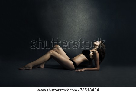 The beautiful woman lying on ground and looking up to the light - stock photo