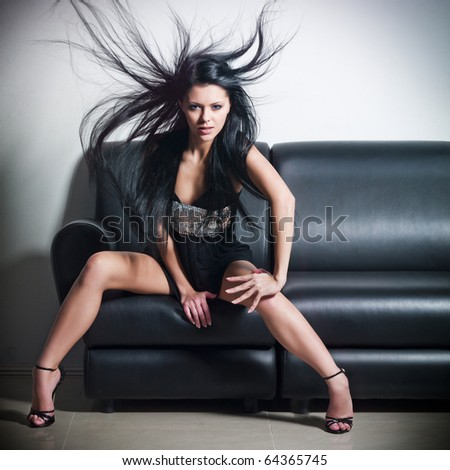 The beautiful woman sitting on a leather sofa - stock photo
