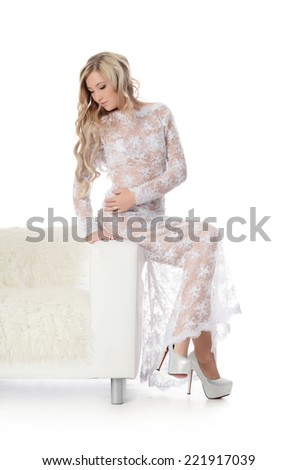 The beautiful woman. The woman in a white dress on a white sofa. isolated on white background - stock photo