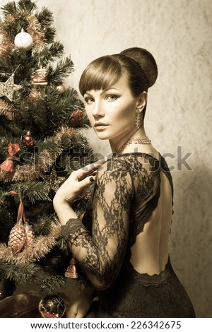The beautiful woman with a make-up,a hairdress, in evening dress, posing near the Christmas tree. Vintage retro color toned photo - stock photo