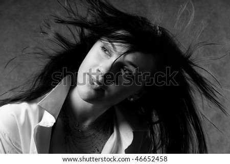 The beautiful woman with dark hair in a white shirt - stock photo