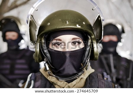 The beautiful young girl in a military uniform and a helmet