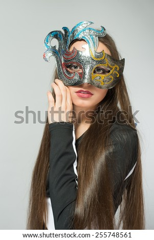 The beautiful young girl in a mysterious mask - stock photo