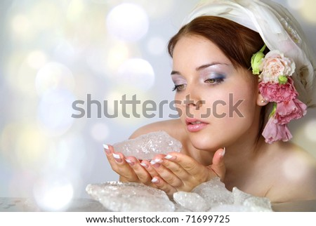 The beautiful young girl in a role of spring which heats winter ice