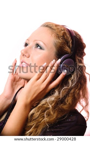 The beautiful young girl in earphones listens to music - stock photo