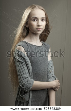 the beautiful young girl in grey dress and grey sweater