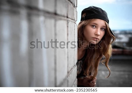 The beautiful, young girl looks out because of edge of a wall. - stock photo