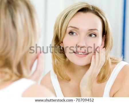 The beautiful young girl with a clean fresh skin touches with a hand a cheek - stock photo