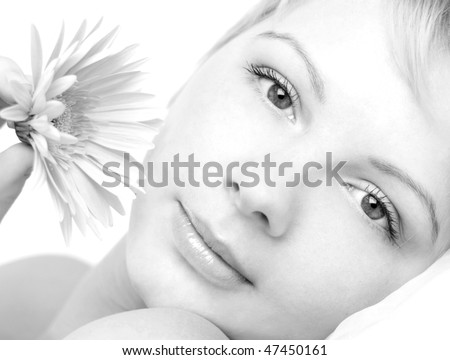 The beautiful young girl with a flower looks at camera