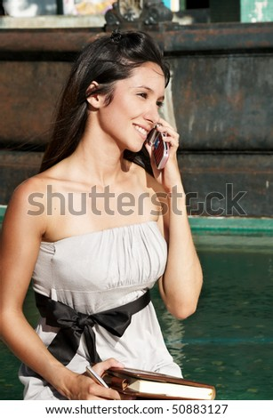 The beautiful young girl with mobile phone - stock photo