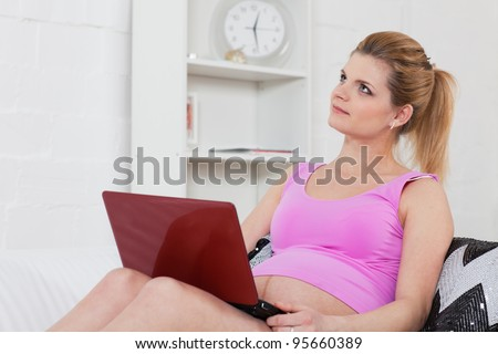 The beautiful young pregnant woman with laptop sits on the house sofa. - stock photo