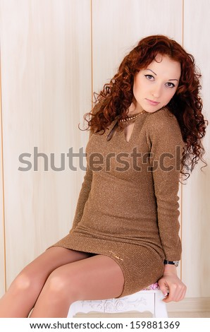 The beautiful young red-haired girl in studio - stock photo