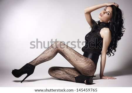 the beautiful young sexy girl in stockings poses in studio - stock photo
